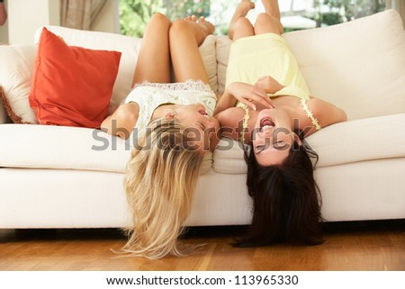 Two Female Friends Lying Upside Down On Sofa - stock photo