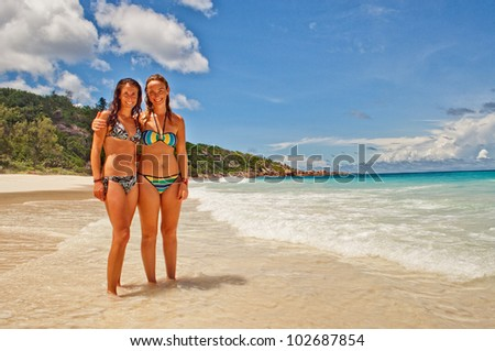Two female friends on tropical island beach vacation  in the warm sunny Seychelles island oceans and palm trees - stock photo