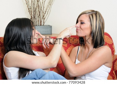 Two female friends or sisters goof off on a couch - touching each others nose