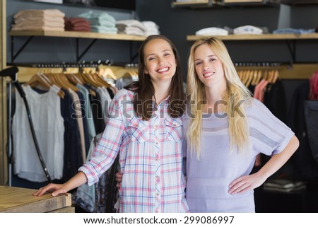 Two female friends standing together and smiling at camera in clothes store