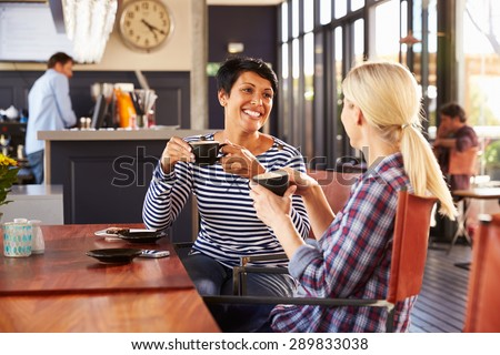 Two female friends talking at a coffee shop - stock photo