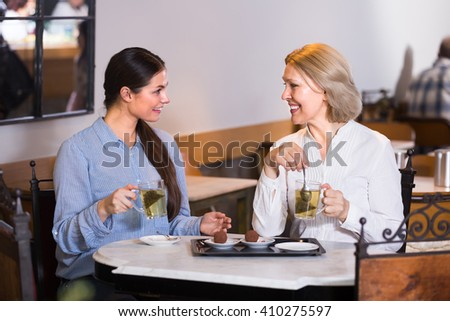 Two female friends talking at cafe table and smiling