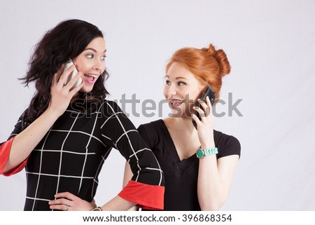 Two female friends talking on their phones together and smiling with pleasure