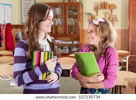 Two female friends with books in classroom
