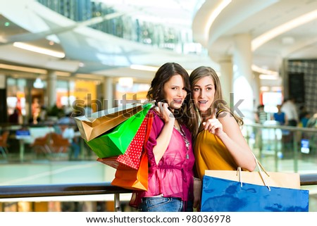 Two female friends with shopping bags having fun while shopping in a mall