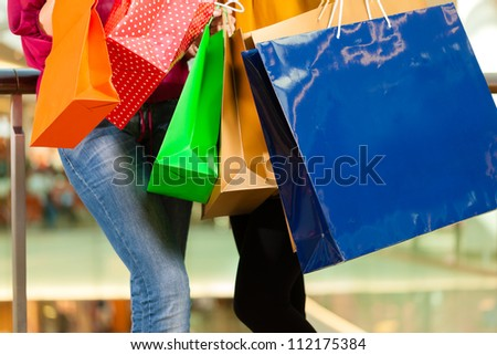 Two female friends with shopping bags having fun while shopping in a mall, close-up on bags - stock photo