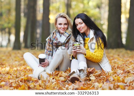 Two female friends with take away coffee in autumn park