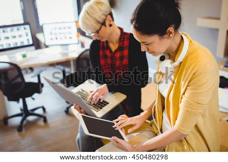 Two female graphic designer using digital tablet and laptop in office - stock photo