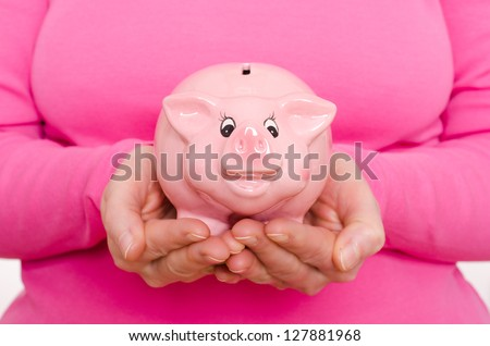 Two female hands are holding a pink piggy bank - stock photo