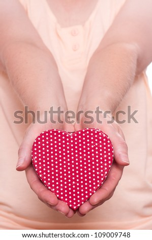 Two female hands are holding a red heart ahead - stock photo