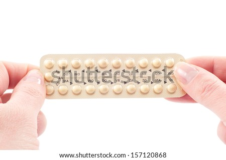 Two female hands holding a strip of contraceptive pills - stock photo