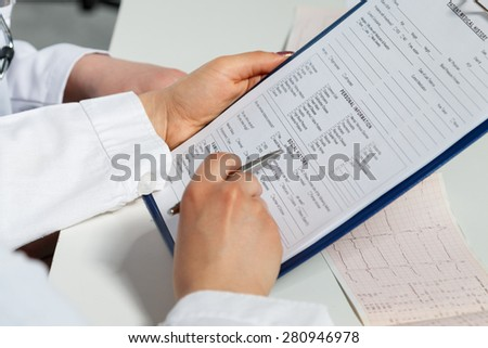 Two female medicine doctors hands examining patient documents. Professional conversation, council of cardiologists. Working conference of colleagues. Medical concept of heart disease treatment - stock photo