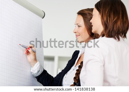 Two female office colleagues attending a seminar standing in front of a blank white flip chart having a discussion and writing with a red marker - stock photo