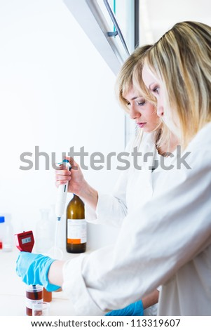 Two female researchers working in a laboratory (color toned image)