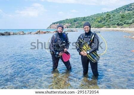 Two female scuba divers standing in the sea ready for a dive - stock photo