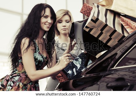 Two female shoppers at the car - stock photo