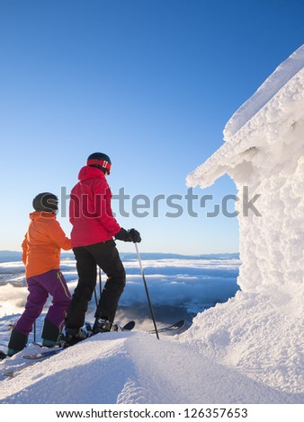Two female skiers standing next to a frosty cabin in the afternoon sun.