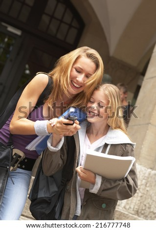 Two female students looking at a mobile phone. - stock photo