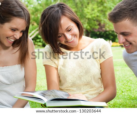 Two female students reading a book on the grass - stock photo