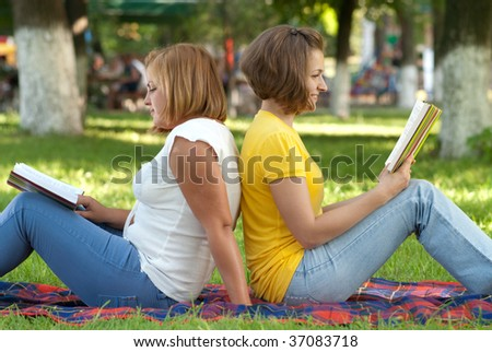 Two female students studying at campus park