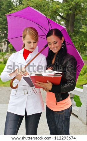 Two female students under umbrella outdoors