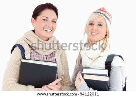 Two female students with books looking to camera