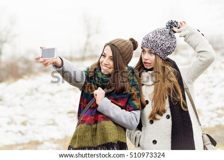 Two female teenage friends taking a selfie outdoors in winter. Cheerful fun girls photographing themselves on phone outside on snowy day making funny faces wearing winter fashion clothes and hats.