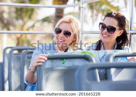 two female tourist taking open top bus touring the city - stock photo