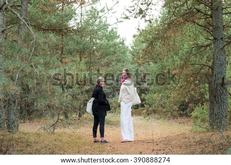 Two female tourists walking in the forest