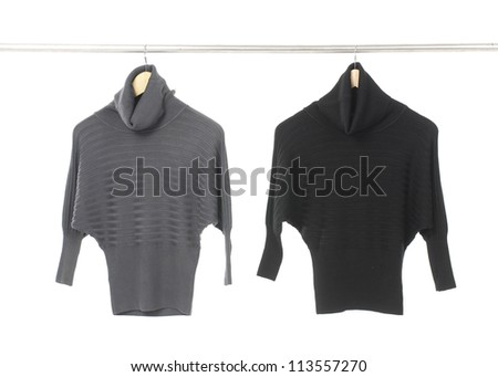 Two Female winter grey and black pullover on a hanger - stock photo