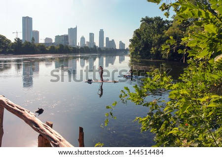Two females paddle boarding on Ladybird Lake with downtown Austin, TX in the background. - stock photo