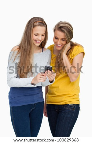 Two females student smiling while looking a cellphone against white background - stock photo