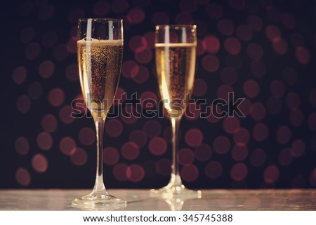 Two festive champagne glasses on holiday bokeh background, selective focus on first glass