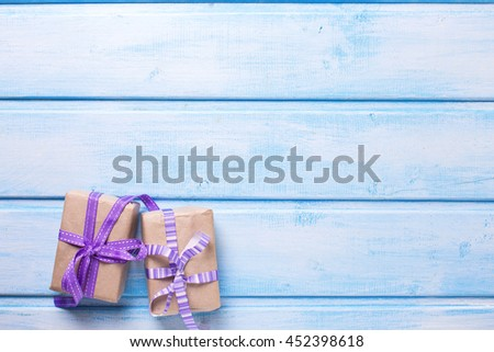 Two festive gift boxes with presents on blue wooden background. Selective focus. Place for text. - stock photo