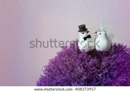 Two figures of lovers white doves in veil and hat sitting on a purple Bush on a white background. Wedding day