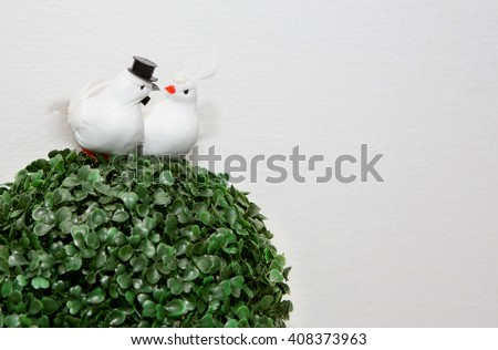Two figures of lovers white doves in veil and hat sitting on a tree on a white background. Wedding day