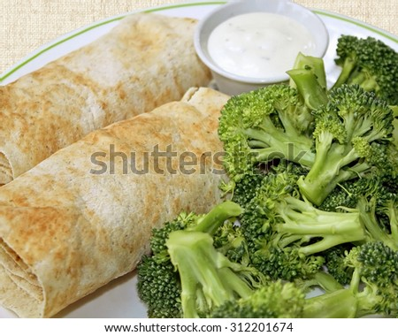 Two filled Tortilla wraps with a side of fresh raw broccoli and a container of creamy dressing for dipping - stock photo