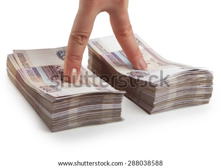 Two fingers of a hand at the stacks of Russian paper money - stock photo