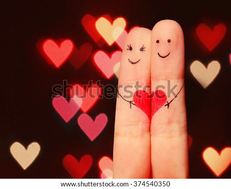 Two fingers with painted smiley faces and heart over bokeh background. Happy Couple Concept