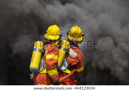 two firefighter in fire fighting suit spraying high pressure water to fire and black smoke - stock photo