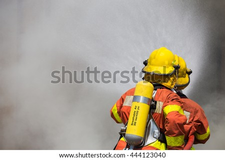two firefighter in fire fighting suit spraying high pressure water to fire and smoke - stock photo