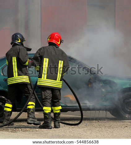 two Firefighters extinguished the fire at a car after the traffic accident