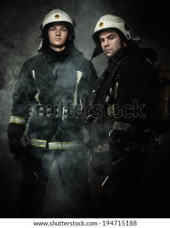 Two firefighters with axes in a smoke - stock photo