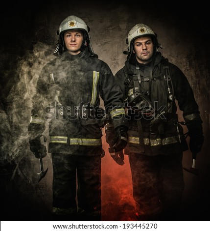 Two firefighters with helmet and axe in a smoke - stock photo