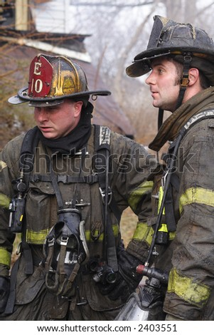 Two Fireman having a discussion while on the job at a fire