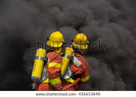 two firemen in fire fighting suit encounter with fire and black smoke - stock photo