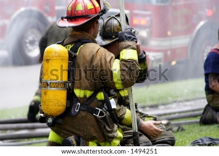Two firemen kneeling at a fire - stock photo