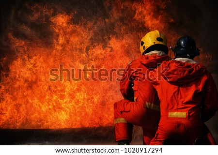 Two Firemen using extinguisher and water from hose for fire fighting at firefight training of insurance group. Firefighter wearing a fire suit for safety under the danger case.