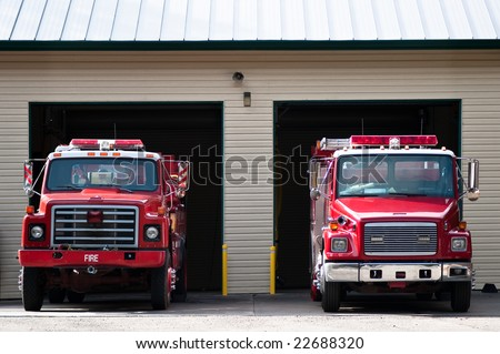 Two firetrucks parked and ready to roll - stock photo