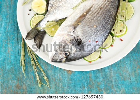 Two fish dorado with lemon on plate on blue wooden table close-up - stock photo